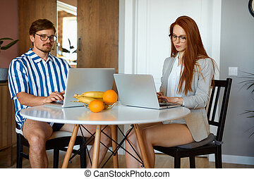 married couple work on laptop at home