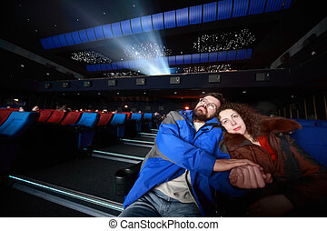 Married couples sit on concert and hug, focus on husband