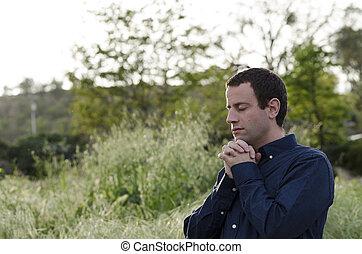 Married man praying outside in a grassy field.