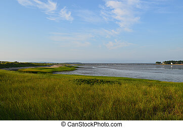 Summer skies over Duxbury Bay with marsh grass and sand.