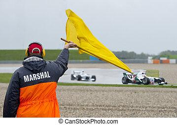 Marshal waving yellow flag