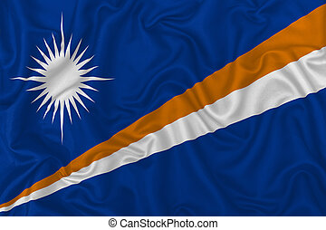 Marshall Islands country flag on wavy silk textile fabric background.