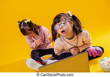 Cute girl with two tails looking in camera while her sister sitting behind