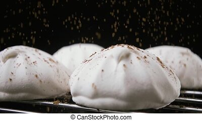 Marshmallow sprinkled with cocoa powder. Slow motion