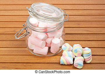 Marshmallows in the glass jar on wooden background