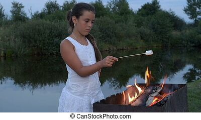 Marshmallows on camping fire - A pretty little girl fries...