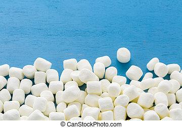 Marshmallows - Small round white marshmallows on blue...