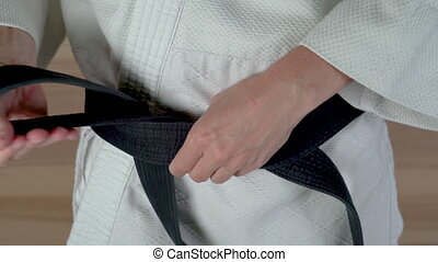 Putting on martial arts black belt with white uniform.