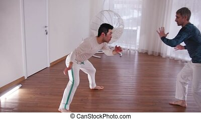 Martial arts. Capoeira. Two young men training. Mid shot