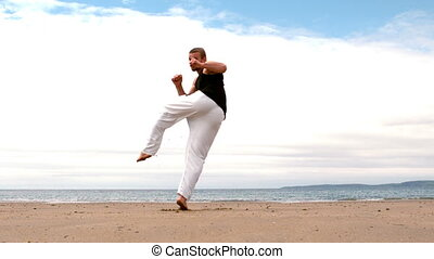 Martial arts expert practicing on the beach in slow motion