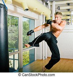 Martial Arts Flying - Kickboxer kicking the sandbag