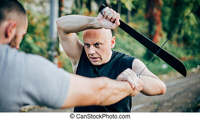 Martial arts instructor demonstrates machete fighting. Long...