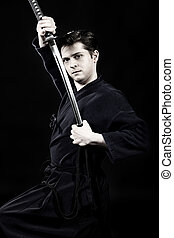 martial man - Handsome young man practicing kendo. Over dark...