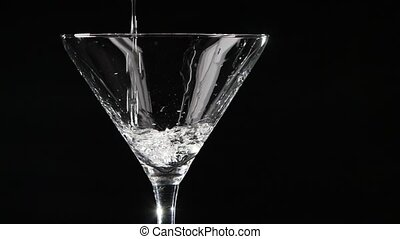 Martini being poured into a glass on black background. Slow motion.