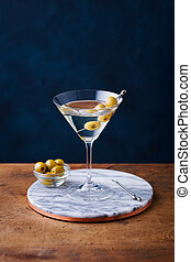 Martini cocktail with green olives on marble board. Wooden table. Blue background.