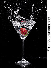 Martini drink splashing out of glass, isolated on black ...