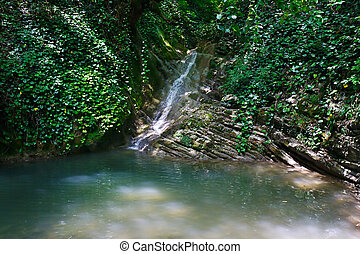 Marvellous waterfall among the rocks in mountain forest