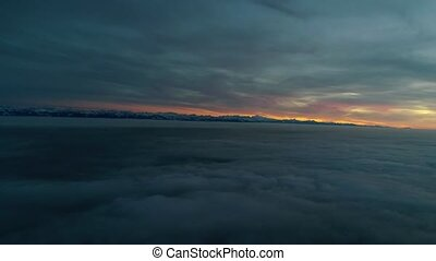 Marvelous aerial drone panorama flyover in orange warm evening sunset sky over dense fog cloud mountain hill landscape