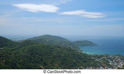 marvelous hilly landscape with green forests and small building silhouettes near blue endless ocean under sky with white clouds