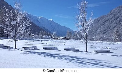 Marvelous time lapse aerial drone flight over snow covered pine tree winter forest in cozy house Alps mountain landscape