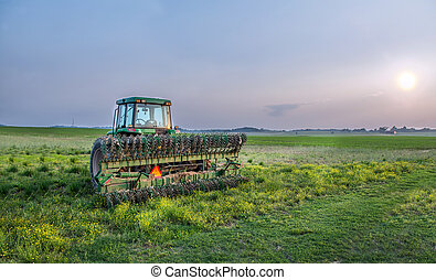 Maryland farm with tractor and tiller in a field at sunset