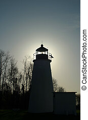 Lighthouse silhouetted by morning sun