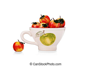 Marzipan apples in a ceramic cup isolated on white background