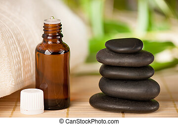 Masage rocks and bottle of aromatherapy oil