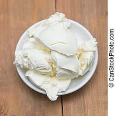 mascarpone cheese in white bowl on wooden background