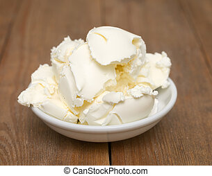 mascarpone cream cheese in glass bowl on wooden background