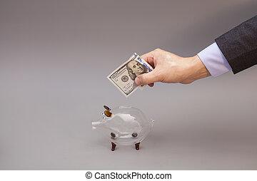 maschio, mano, mettere, cento dollari, conto, in, vetro, banca piggy, isolato, su, grigio