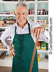 maschio, proprietario, con, bastone, standing, in, negozio