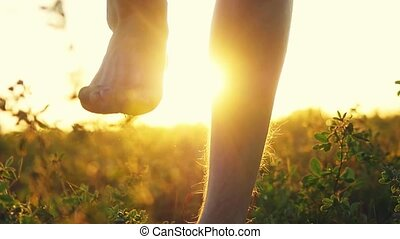 Masculine feet go barefoot to the soft grass through the sun during amazing sunset with lense flare effects in slow motion. 1920x1080