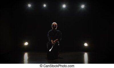 Masculine Kendo fighter practicing martial art with the...