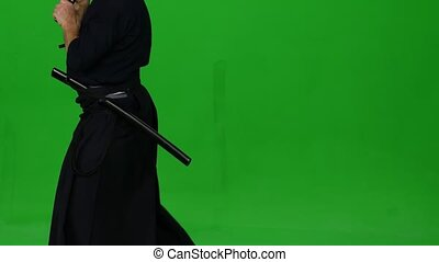 Strong Kendo warrior wearing in an armor and traditional kimono is performing martial art with the bamboo bokken in the twilight against on green screen. Combat training. CLose up