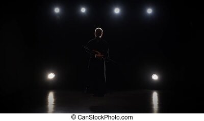 Masculine Kendo warrior practicing martial art with the...