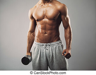 Studio shot of a male model in sweatpants holding dumbbell on grey background. Shirtless muscular man working out. Health and fitness theme.