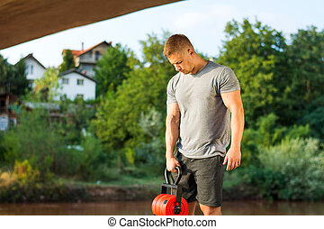 Masculine man with dumbbell outdoors