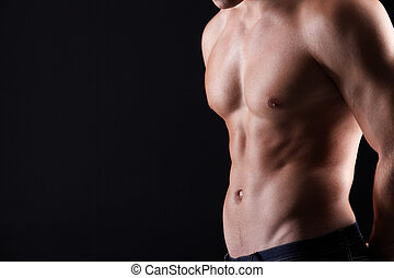 Masculinity - Torso of strong man in jeans against dark...
