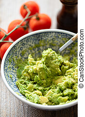 Mashed avocado in bowl. Chunky guacamole sauce