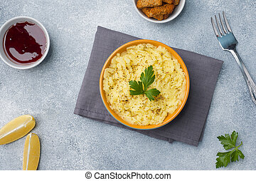 Mashed potatoes with herbs, croutons and lemon in a plate on napkins.