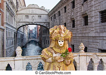 """Carnival mask in a yellow costume in front of the """"Ponte dei Sospiri"""", Venice in Italy"""
