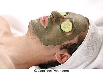 someone having a mud mask in a spa with cucumbers
