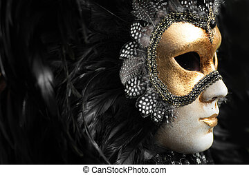 Venetian mask decorated with gold leaf and embedded with fowl feathers.