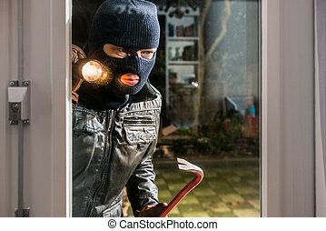 Masked burglar with flashlight and crowbar looking into glass window of house