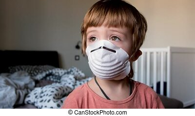 Young boy with protective mask looking out the window at home quarantine