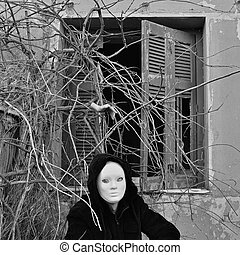 Masked figure and cut hand creeping though overgrown branches at haunted house.