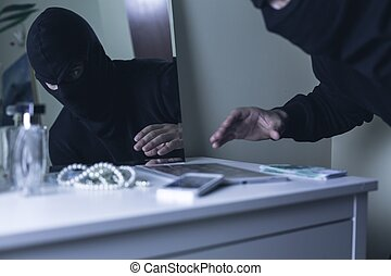 Masked intruder during robbery - Photo of masked intruder...
