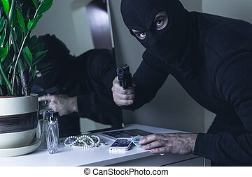 Masked intruder with gun