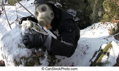 Strange man in gas mask acting hostile in front of a cave entrance, defending territory. Post-apocalyptic concept, climbing out of underground shelter